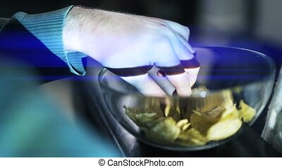 Close up shot of hands taking a crisp from a bowl. - Hands...