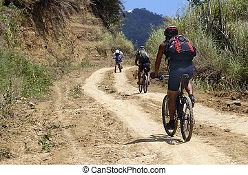 Mountain Bikers - Mountain bikers push uphill towards the...