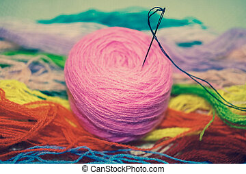 a tangle of pink thread for embroidering on a colored background with needle