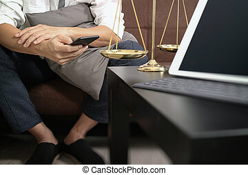 Justice and Law context.Male lawyer hand sitting on sofa and working with smart phone,digital tablet computer docking keyboard with gavel and document on living table at home