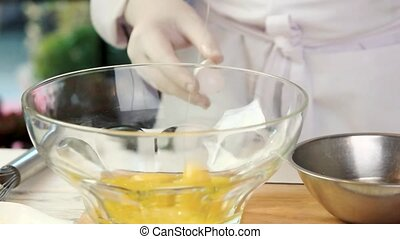 Bowl with egg yolks. Hand of chef holding eggshell.