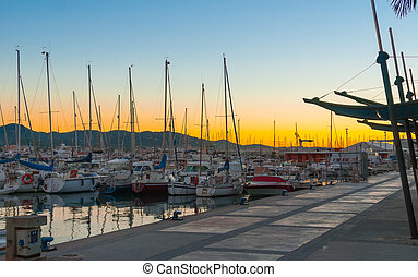 Magnificent golden sunset color in marina harbor.  End of a warm sunny day in Ibiza, St Antoni de Portmany, Spain.