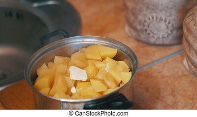 Piece of Butter Falls into the Potatoes in a Saucepan on the...