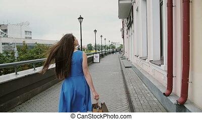 Wind blows long dark hair beautiful young woman walking down...