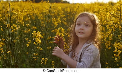 Girl standing amidst of field at sunset. Slow mo - little...