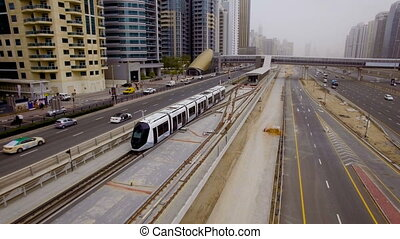 modern tram travels on rails along the high-rise buildings...