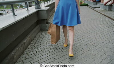 legs slender young woman, walking in the city down the street past the store with shopping bags, slow mo, stedicam shot