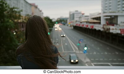 beautiful girl standing on the bridge, looks at the city,...