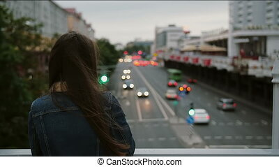 beautiful girl standing on bridge, looks at the city, then...