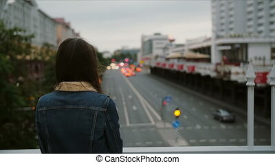 beautiful girl standing on bridge, looks at the city, then turns to the camera and smiling. Wind blows her hair. slow mo
