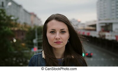 serious beautiful girl standing on the bridge, looks at camera, than started to smile. Wind blows her hair . slow motion