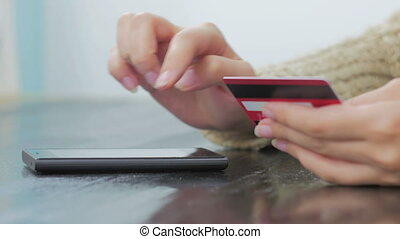 Woman shopping online at smartphone with credit card - Young...