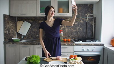 Funny woman housewife shoot selfie with cellphone while cooking in the kitchen at home indoors