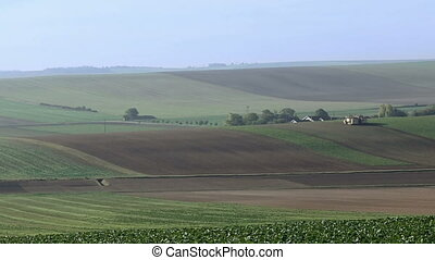 Cultivated farm field landscape in France. Green hills over...