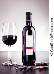 Red wine bottle and glass with wine tools - a blank labeled...