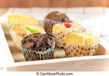 Cupcake various flavors in wood tray on wood table.