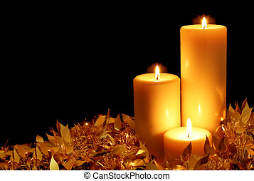 Candlelight, with golden tinsel, against black background.