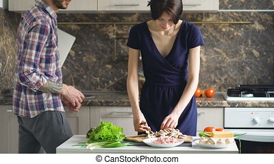 Happy couple cooking on the kitchen while man kiss her girlfriend at home