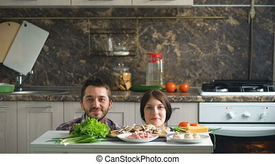 beautiful smiling couple play and kiss above the table with vegetables while cooking in kitchen