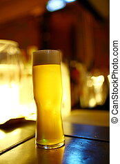 A glass of beer on the bar