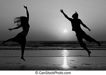 Silhouettes of happy couple jumping at the beach. -...
