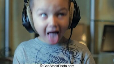 The boy listens to hard rock in headphones - The boy listens...