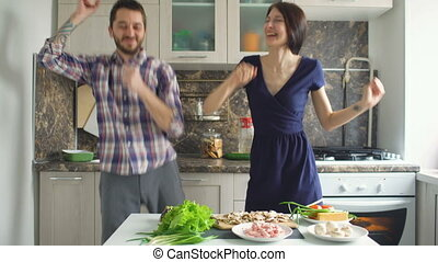Happy beautiful couple dancing and kissing while cook on the kitchen at home