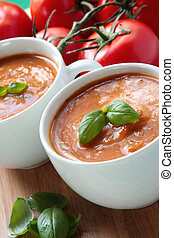Tomato Soup - Cups of tomato soup with basil leaves.