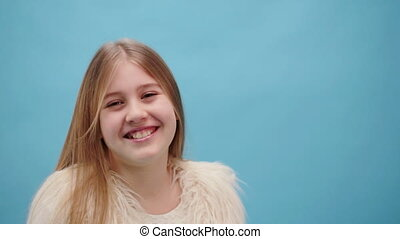Pretty young girl laughing on blue background