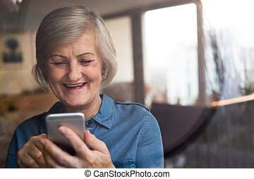 Senior woman with smartphone at home sitting at the window -...