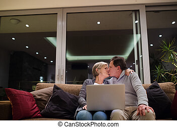 Seniors with laptop sitting on a couch, kissing - Beautiful...