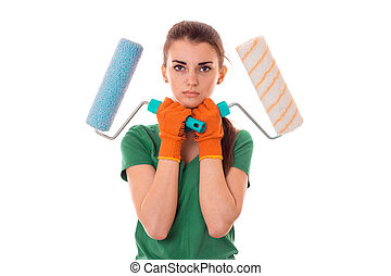 a young girl in the green shirt is worth having and holding the hands of two rollers for painting