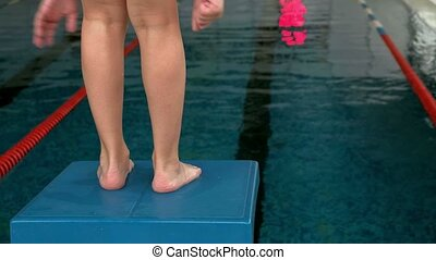 boy awkwardly dives into the pool - On the starting blocks...