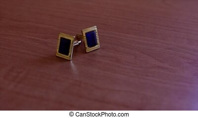 gold cufflinks lie on wooden floor.