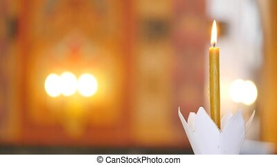 Single candle with dripping wax and blurring lights of many candles in two candlesticks at background
