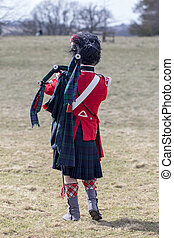 Scots guards piper on field with bagpipes - Scots guards...