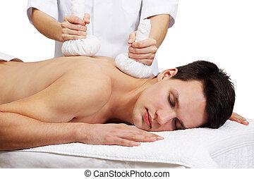 Thai Ball Massage. Man getting SPA thai herbal compress...