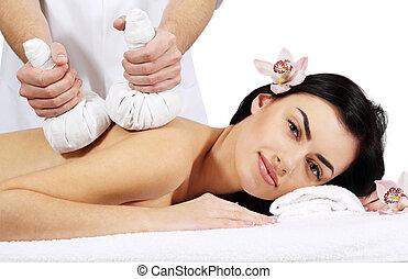 Thai Ball Massage. Woman getting SPA thai herbal compress...