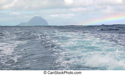 Wavy ocean and distant island, view from the ship - View...
