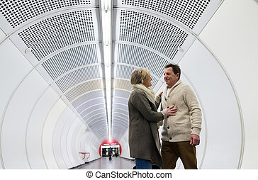 Senior couple in winter clothes in hallway of subway hugging