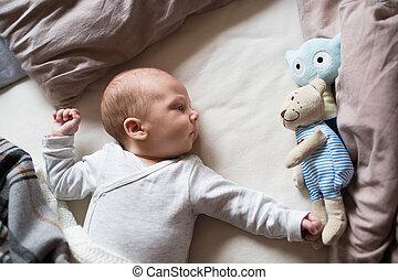Cute newborn baby boy with teddy bear lying on bed - Cute...
