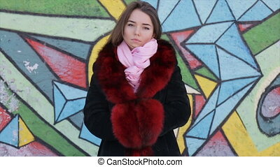 The girl in a fur coat on the background of painted wall -...