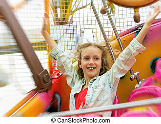 Happy little girl having fun in amusement park.
