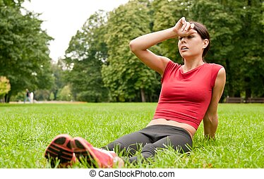 Relax in grass - tired woman after sport