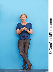 handsome man leaning against blue wall and using cell phone...