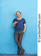 Full body happy man standing by wall with mobile phone -...