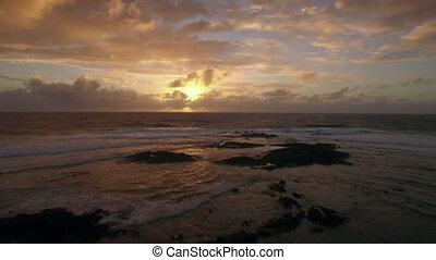 Aerial view of ocean in golden light of sunset - Flying over...