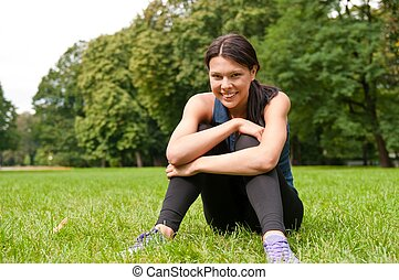 Relax - sportswoman sitting in grass