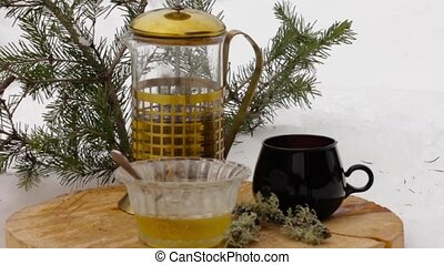 tea set with honey: pouring hot tea from transparent teapot...