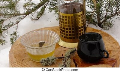 tea set with honey: pouring hot tea from transparent teapot to black cup on a wooden stand among the snow
